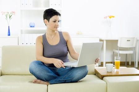 telework: Young woman sitting on sofa at home working on laptop computer. Stock Photo