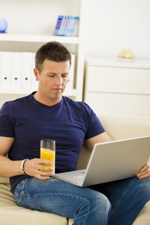 sinecure: Man sitting on sofa at home and using laptop computer.