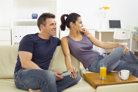 Happy young couple sitting on sofa at home, watching TV. Stock Photo - 4535105