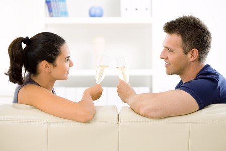 Love couple clinking champagne glasses at home on sofa. Smiling and looking at camera. photo