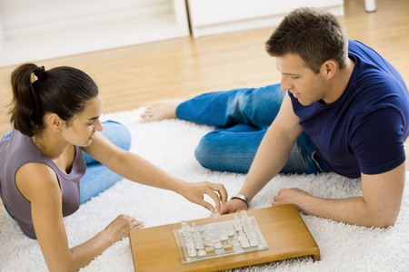 Relaxed young couple playing chess at home lying on floor. photo