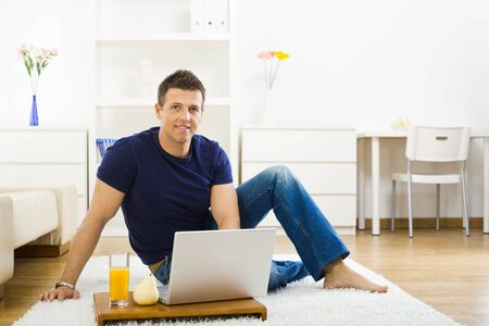 outworking: Casual young man using laptop computer at home, sitting at floor, smiling and lloking at camera.