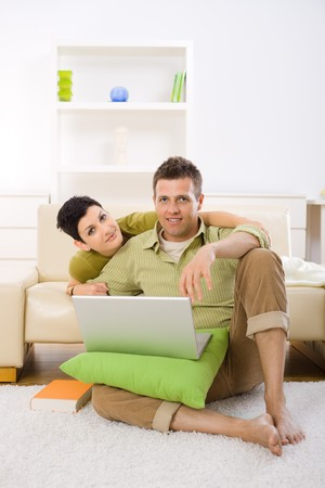 Young couple using laptop computer at home, sitting on floor and lying on couch, embracing. Stock Photo - 4535079