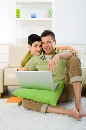 Young couple browing internet at home on laptop computer, sitting on floor and lying on couch, embracing. photo