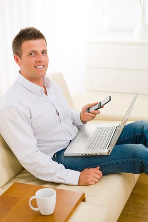 Casual businessman working at home sitting on couch, using laptop computer and mobile phone. Stock Photo - 4535103