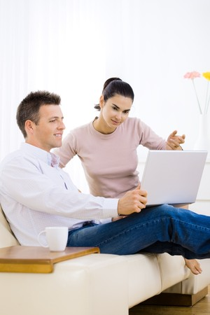 Young couple browsing internet at home, using laptop computer, sitting on couch, smiling. Stock Photo - 4535006