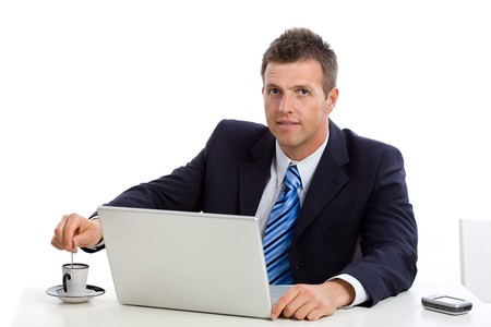 Businessman stirring his coffee besides while working on laptop computer. photo