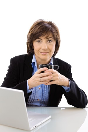Senior businesswoman using laptop computer while drinking coffee, looking at camera. Isolated on white background. photo