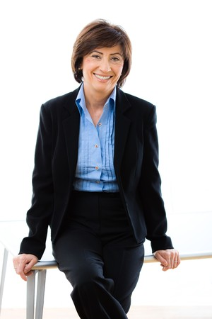 undoubting: Studio portrait of senior businesswoman in black suit and blue shirt, sitting on table, smiling and looking at camera. White background.