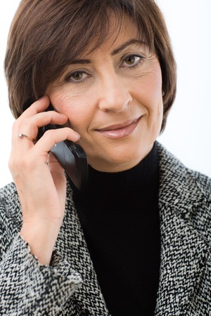 Closeup portrait of senior businesswoman talking on mobile phone. Isolated on white background. photo