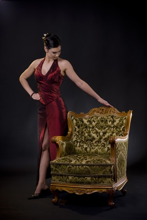 Beautiful young woman wearing evening dress posing withcarved wood armchair, on dark background. photo