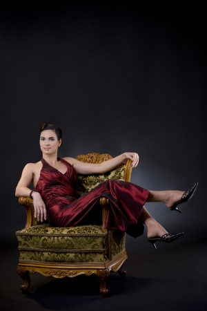 Beautiful young woman wearing evening dress lsitting in carved wood armchair, on dark background. photo