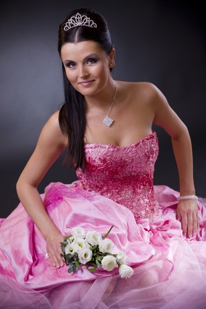 Smiling young bride posing in a pink wedding dress, holding bouqet of white flowers.