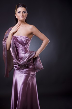 formal attire: Studio portrait of a young woman wearing a light purple evening dress with stole. Stock Photo