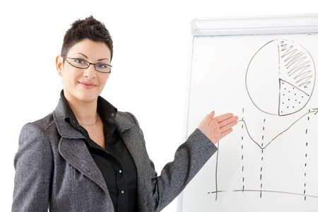 gratified: Happy young businesswoman presenting at whiteboard, smiling, isolated on white background.