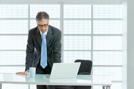 Worried businessman leaning on office desk with laptop computer on it,  looking down.  photo