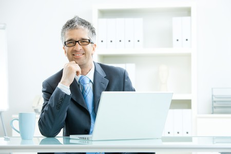 Businessman with grey hair, wearing grey suit and glasses thinking over laptop computer, sitting at desk in bright, modern office, leaning on hand, smiling. Stock Photo - 4555517