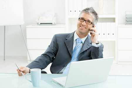Businessman sitting at desk in bright office, talking on mobile phone and smiling. photo