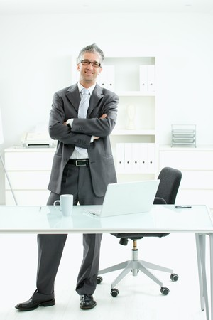 Satisfied, smiling businessman standing arms crossed behind office desk with laptop computer and coffee cup on it. photo