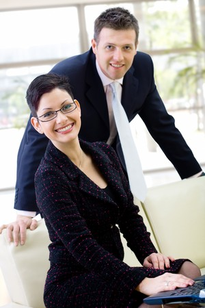 Happy business people sitting at office lobby, smiling. photo