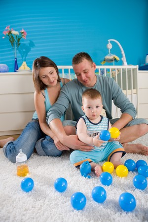 1 year old: Portrait of happy family at home. Baby boy ( 1 year old ) and young parents father and mother sitting on floor and playing together at childrens room, smiling. Stock Photo