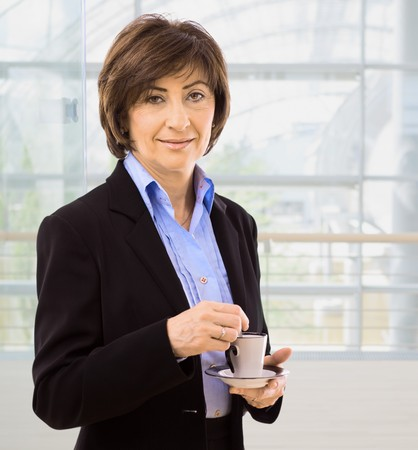 Senior businesswoman drinking coffee, standing in fron of office windows. photo