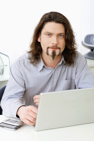 busy beard: Portrait of casual businessman working at desk using laptop computer, looking at camera. Stock Photo