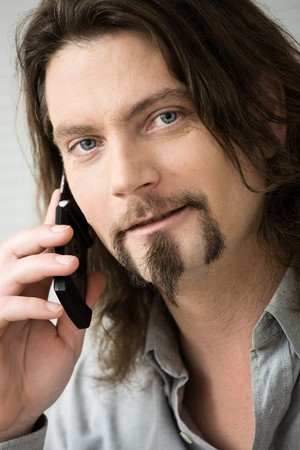 busy beard: Closeup portrait of bearded man wearing grey shirt talking on mobile phone.