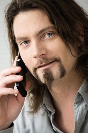 hombre con barba: Closeup retrato barbudo hombre vestido de camisa gris hablando por tel�fono m�vil.