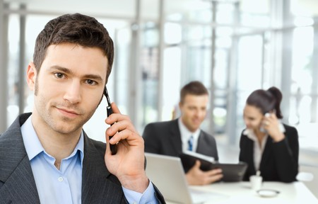 gratified: Young smiling businessman calling on phone, business meeting at background.