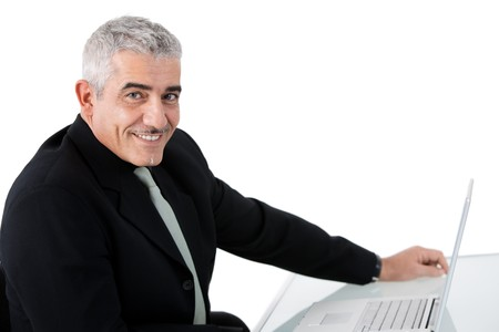 Mature businessman working on laptop computer at desk az office, smiling, isolated on white background. photo