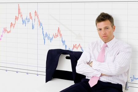 Disappointed businessman sitting in front of chart showing economic recession.  photo