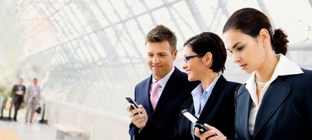 calling on phone: Happy businesspeople using mobile phones at office lobby - plenty of copyspace. Stock Photo