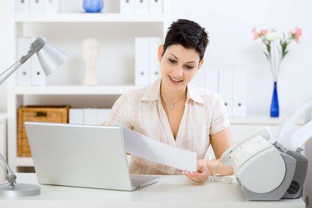 sending: Casual joven empresaria de trabajo en casa, leer un fax.