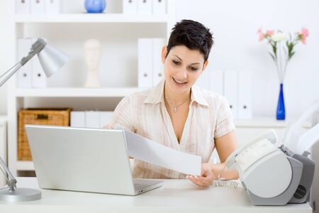 Casual young businesswoman working at home, reading a fax. Stock Photo