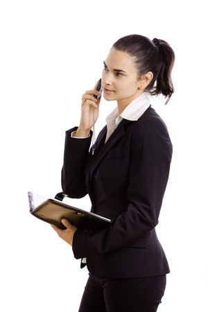 Young businesswoman wearing black suit, holding personal organizer talking on mobile phone. Isolated on white background.