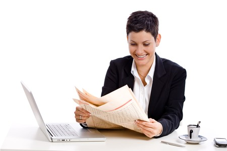 Businesswoman reading financial newspaper, white background. Stock Photo - 4559818