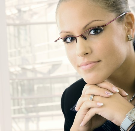 woman wearing glasses: Young businesswomen wearing glasses. Thinking, leaning on hands, looking at camera.