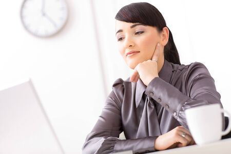 undoubting: Young businesswoman thinking in her office leaning on her hand.