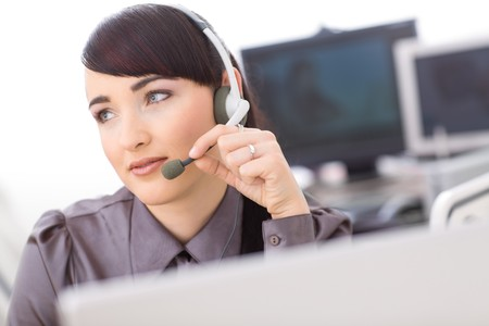 Young female customer service operator talking on headset, holding the microphone. photo