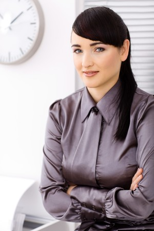 Young businesswoman siitting arms crossed in the office, smiling and looking at camera. photo