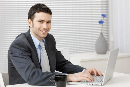 Happy young businessman working on laptop computer at office, smiling. Stock Photo - 4560073
