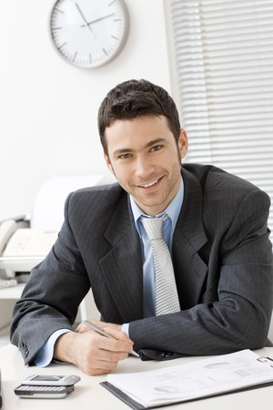 gratified: Happy young businessman working at desk at office, smiling.