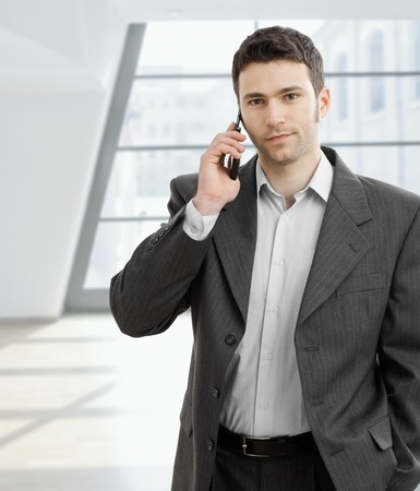open collar: Casual businessman talking on mobile phone, standing in office lobby. Stock Photo