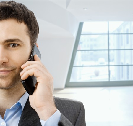 open collar: Closeup portrait of casual businessman talking on mobile phone, standing in office lobby.