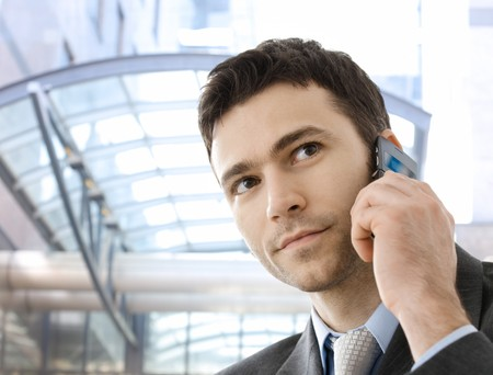 Young businessman calling on mobile phone, outdoor. photo