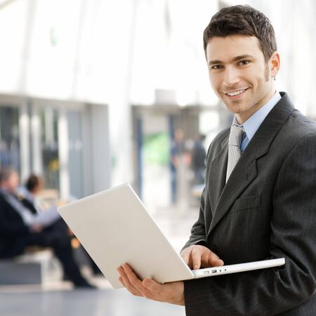 office lobby: Portrait of successful young businessman at corporate location. Stock Photo
