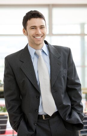 Happy businessman standing with hands in pocket in office lobby, looking at camera, smiling.  Stock Photo - 4560100