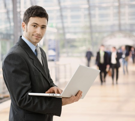 Young smiling businessman using laptop on corporate location, indoor. photo