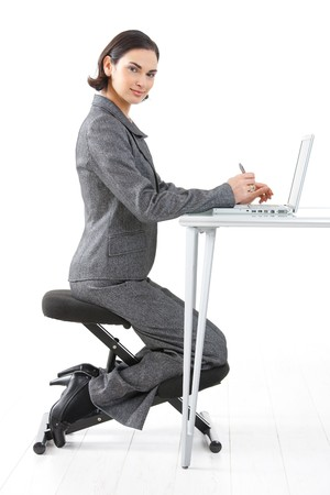 Young happy businesswoman working on kneeling chair, smiling, isolated on white. Stock Photo - 4560125